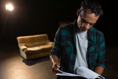 Actor reading their scripts on stage Stock Photography