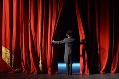 Actor in a tuxedo stage curtain opens. Actor in a tuxedo opens the stage curtain in the theater Stock Images
