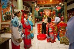 Actores des chinesischen Theaters in den historischen Kostümen, die inneren alten buddhistischen Tempel praing sind Stockbild