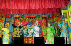 Actores van het Chinese theater die op het stadium met heldere gordijnen van traditionele opera dansen Royalty-vrije Stock Afbeeldingen