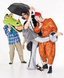 Actors clowning. A group of theatrical people clowning around in colorful costumes, dressed individually as a crocodile, landlord, woman in spacesuit and a stock photography