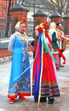 Actors dressed in colorful national costumes greet people on the street. Stock Image