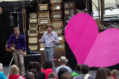 Actors near a big pink heart. AURILLAC, FRANCE - AUGUST 20: two comedians play close to a big pink heart as part of the Aurillac International Street Theater Stock Photos