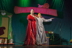 The actors on the stage of children's theater in the red and white raincoat Royalty Free Stock Photography