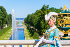 Actress in ancient costume welcomes tourists in Peterhof Palace Stock Image