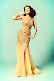 Actress. Fashion shot of a stunning woman in luxurious golden dress. Full length portrait Stock Photography