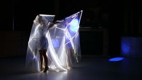Actress girl in white LED wings. Two beautiful actress girl in white clothes and unusual white wigs dancing with LED wings that glow on the stage under the stock video footage