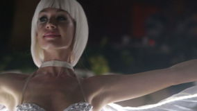 Actress girl in white LED wings. Two beautiful actress girl in white clothes and unusual white wigs dancing with LED wings that glow on the stage under the stock video