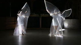 Actress girl in white LED wings. Two beautiful actress girl in white clothes and unusual white wigs dancing with LED wings that glow on the stage under the stock footage