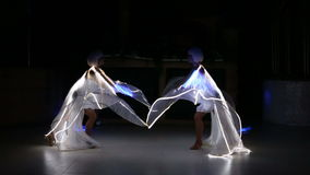 Actress girl in white with LED wings. Two beautiful actress girl in white clothes and unusual white wigs dancing with LED wings that glow on the stage under the stock video footage