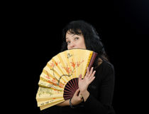 Actress hides her chin behind folding fan Royalty Free Stock Image