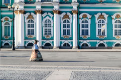 Actress in the image of court lady walks on Palace Square on the background of the Hermitage Royalty Free Stock Photography