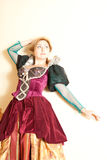 Actress in medieval dress posing against a wall on a light background Royalty Free Stock Photography