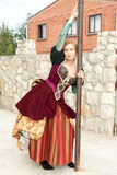 Actress in medieval dress standing near a pole Stock Photos