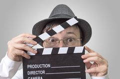 Actress with movie clapper behind face. royalty free stock image