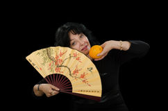 Actress playing with a fan and orange Stock Photo