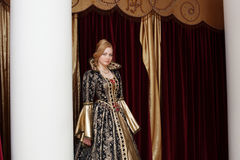 Actress in royal dress posing on curtain backdrop Stock Photography