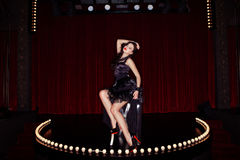 Actress on the stage cabaret. With red curtains and lamps Stock Photo