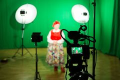 Actress in theatrical costume in a television Studio. Green screen and chroma key. Lighting equipment and filming equipment.  stock photography