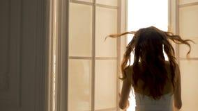 Actrice de femme - ouvre les portes lumineuses, écrit l'étape Elle est habillée dans un beau costume blanc banque de vidéos