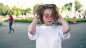 Actriz en gafas de sol rosadas que sonríe a la cámara en el parque del verano, clapperboard almacen de metraje de vídeo