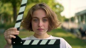 Actriz joven seria que mira la cámara, sonriendo después del clapperboard que es utilizado metrajes