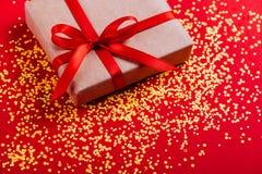 Actual caja con el arco rojo en fondo colorido con confeti multicolor imagenes de archivo