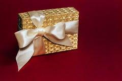 Actual caja de oro con un arco de seda en fondo de color rojo oscuro Copie el espacio foto de archivo libre de regalías