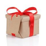 Actual caja del papel marrón con el arco rojo de la cinta Fotos de archivo