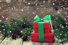Actual caja del rojo con la decoración de la cinta del arco del árbol de abeto y cono de la conífera con efecto mágico de la niev Imagen de archivo libre de regalías