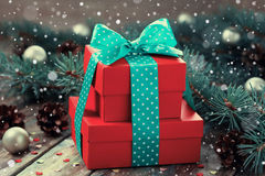 Actual caja del rojo con la decoración de la cinta del arco del árbol de abeto y cono de la conífera con efecto mágico de la niev Fotografía de archivo libre de regalías