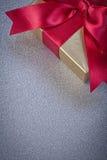 Actual caja envuelta con el arco rojo en estafa gris de los días de fiesta del fondo Fotografía de archivo