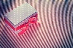 Actual caja envuelta en conce rayado rojo de las celebraciones del mantel Foto de archivo libre de regalías