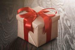 Actual caja rústica con la cinta roja en la tabla de madera Imagen de archivo