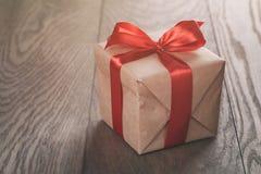 Actual caja rústica con la cinta roja en la tabla de madera Fotografía de archivo libre de regalías