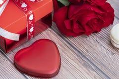 Actual caja, rosa roja, y un pedazo en forma de corazón rojo del metal fotografía de archivo