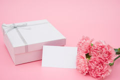 Actual caja y claveles rosados con una tarjeta en blanco Imagen de archivo libre de regalías