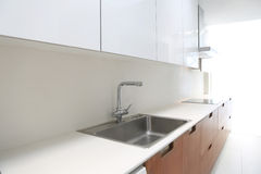 Actual modern kitchen in white and walnut wood. Interior house Stock Photography