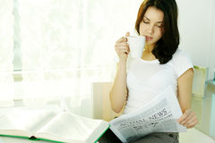 Actual news. Young girl reading newspaper and drinking tea Stock Photos