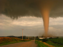 Actual photograph of a tornado at sunset narrowly missing a farm in rural Iowa. A tornado, illuminated by light from the setting sun, narrowly misses a small stock images