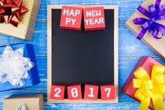 Actuales caja de regalo, pizarra y número de la Feliz Año Nuevo 2017 en r Imagen de archivo