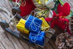 Actuales cajas de regalo de la miniatura en el trineo de Papá Noel como Navidad Foto de archivo