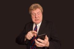 Actualités choquantes Homme mûr étonné dans le costume avec le téléphone portable Image stock
