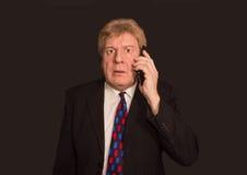Actualités choquantes Homme mûr triste dans le costume avec le téléphone portable Images stock