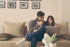 Actualités de lecture de couples sur l'ordinateur portable Photographie stock libre de droits