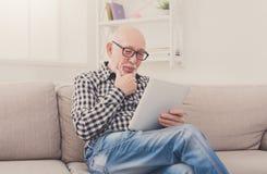 Actualités de lecture d'homme supérieur sur le comprimé numérique Image stock