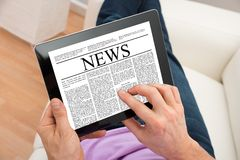 Actualités de lecture d'homme sur le comprimé numérique Photos stock