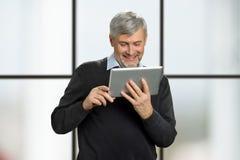 Actualités mûres de lecture de sourire d'homme sur le comprimé Photographie stock libre de droits