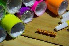 Actualización en los cubos de madera con el papel colorido y pluma, inspiración del concepto en fondo de madera imágenes de archivo libres de regalías