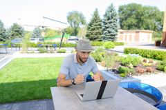 Actuary working with laptop and papers at cafe table. Royalty Free Stock Image